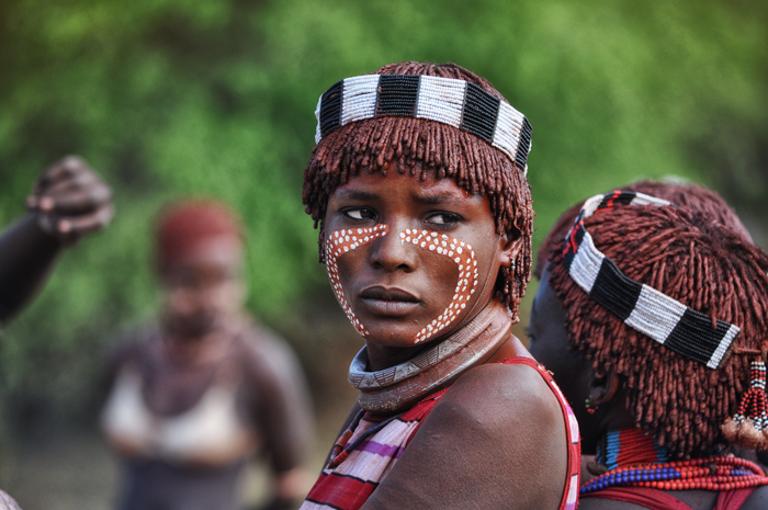 painted face of hamar woman before bull jumping ceremony